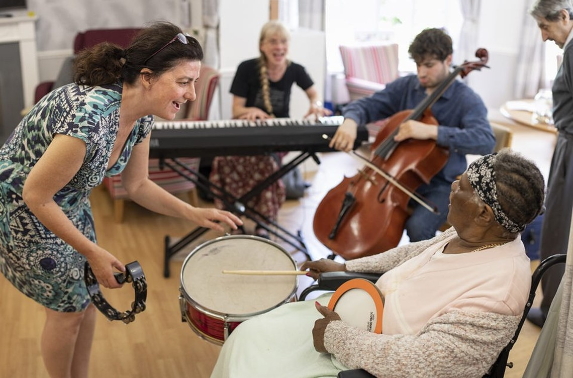 A woman with a tambourine gestures to an elderly lady playing a drum.