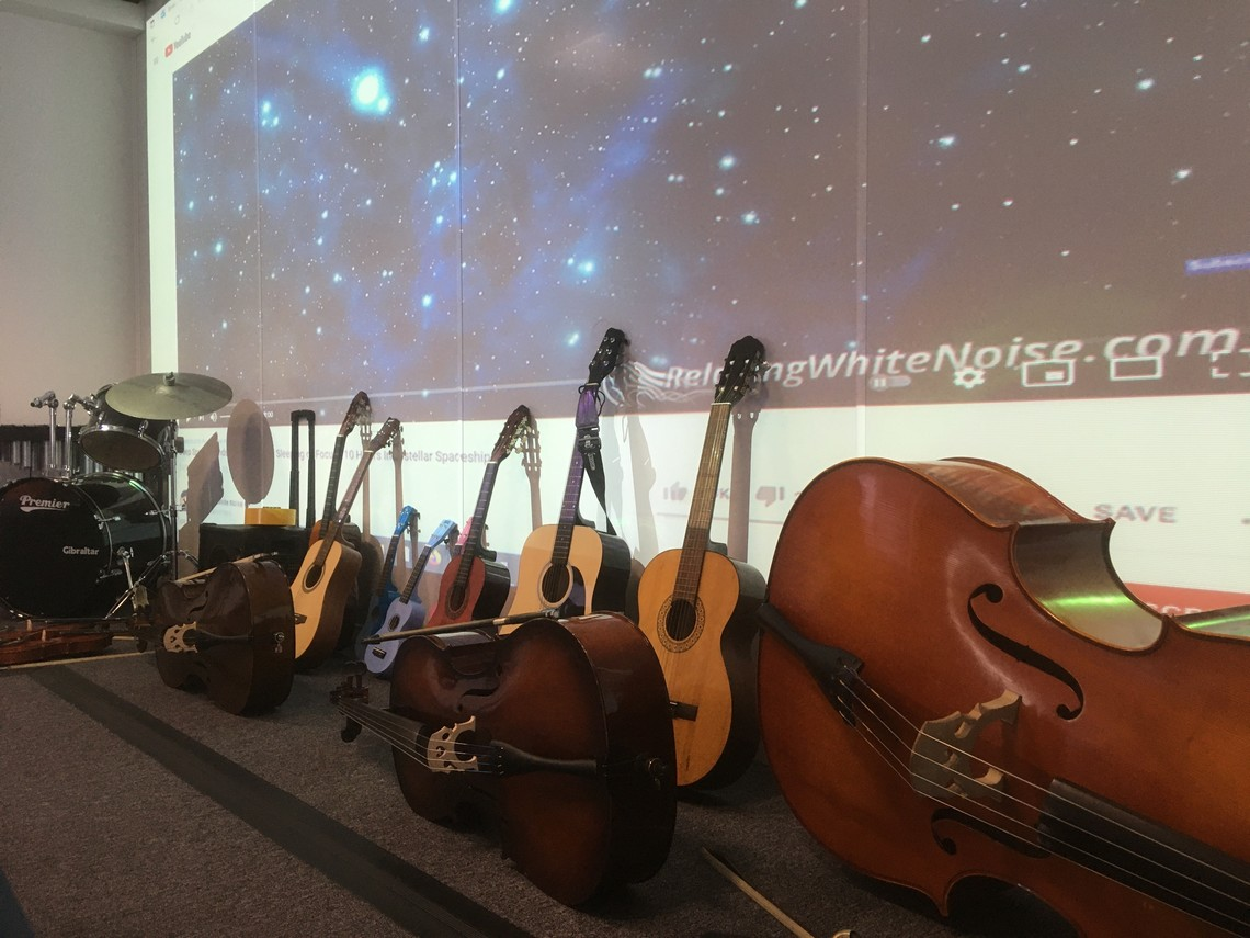 A row of guitars, cellos and a double bass leaning against a wall with a projection of stars on it.