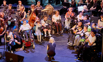 Young musicians in wheelchairs performing on stage using iPads