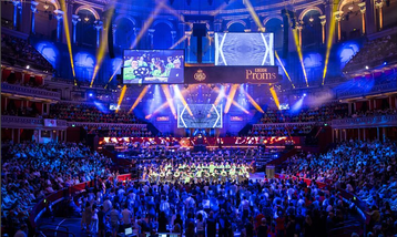 An orchestra on stage at the Royal Albert Hall with a large audience watching.