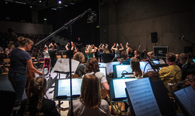 An orchestra and group of dancers rehearsing.