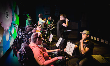 Young musicians performing using wheelchair controllers, a beatboxer on stage in front of them.