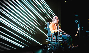A young musician in a wheelchair performing using a wheelchair controller.