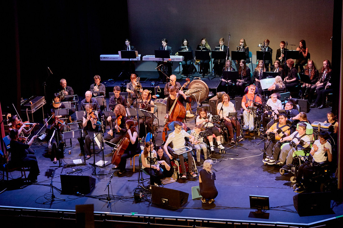 Musicians performing on stage using orchestral instruments young musicians in wheelchairs performing using iPads