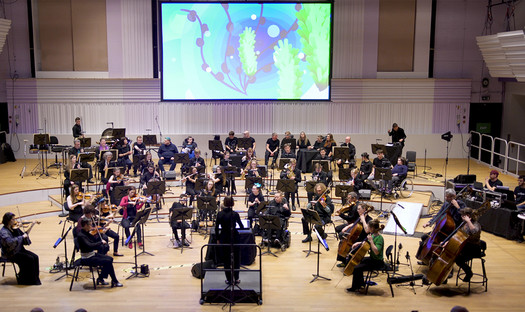 An orchestra of musicians on stage, some in wheelchairs, with a large screen behind projecting graphics.