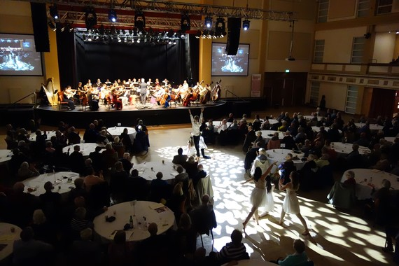 Small groups of dancers perform between round tables of audience members with an orchestra behind on stage