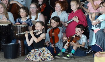 Young children playing orchestral instruments