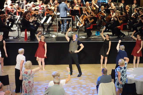 People dancing in front of an orchestra on a stage.