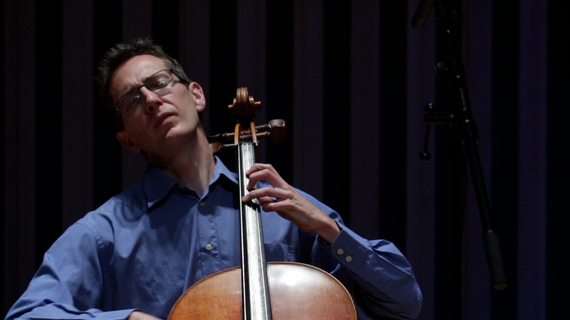 A close up of a man playing the cello.