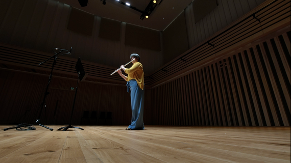 A woman on an empty stage playing flute in front of recording equipment.