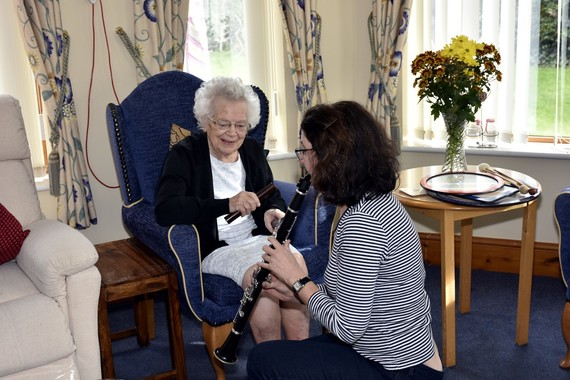 A woman plays clarinet crouching in front of an elderly lady sat in an armchair
