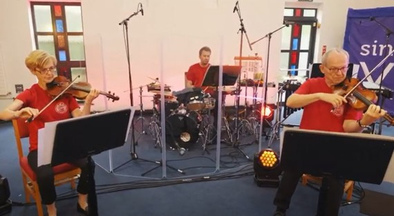 Two violinists play socially distanced, in front of a drummer.