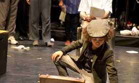 A young boy in a hat putting papers into a briefcase, with performers behind.