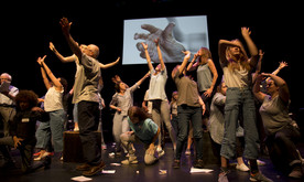 A group of performers on stage with arms outstretched in different directions. A screen behind showing a hand reaching out.