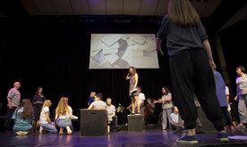 Performers on a stage, one woman in the centre stood on a box, a screen showing a video at the back of the stage