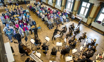 A view from above of an orchestra and care home audience.