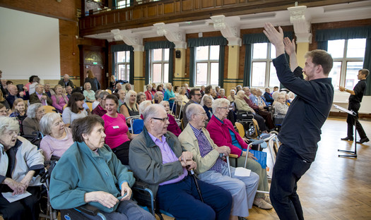 A conductor gesturing to a large audience of care home residents.