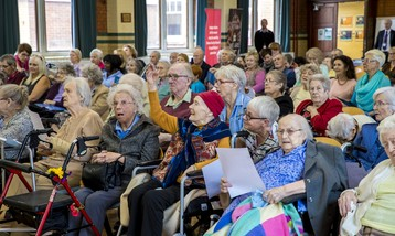 An audience of care home residents, some in wheelchairs.