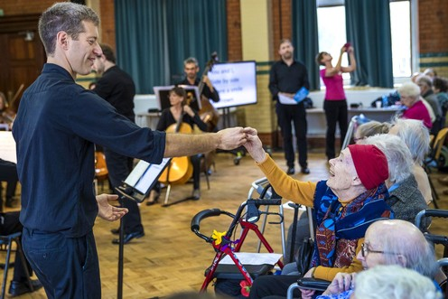Orchestra conductor holds the hand of an elderly lady in the audience.