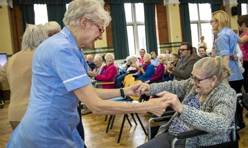 A care home staff member dancing with a seated elderly lady in a wheelchair.