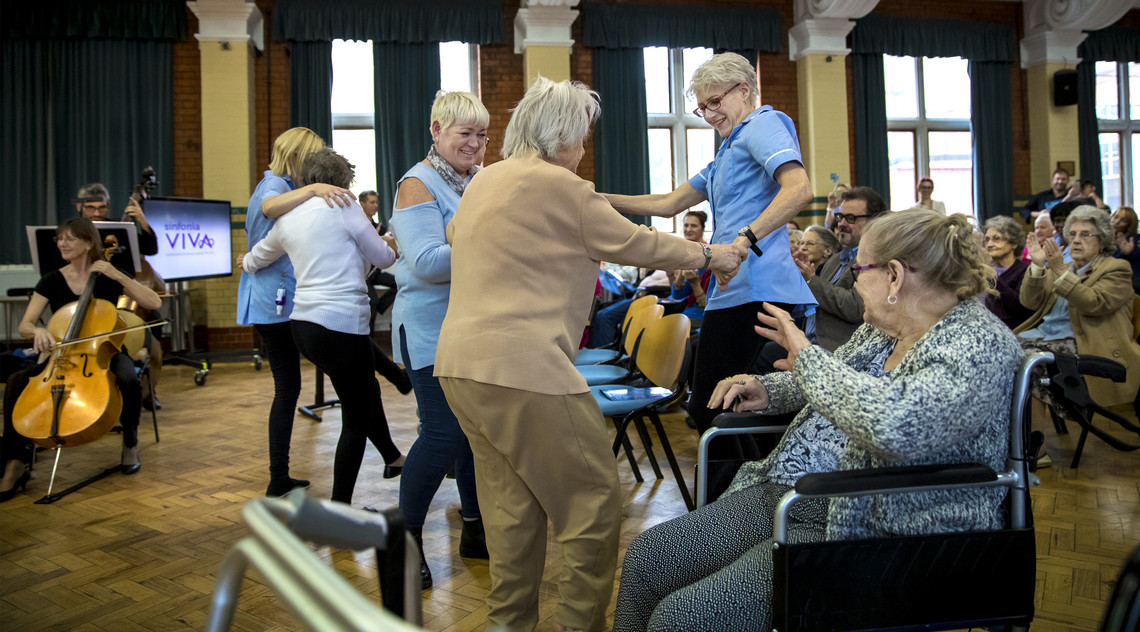 Care home staff and residents dancing in front of an orchestra.