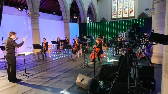 A small socially distanced orchestra play facing a conductor, inside a church with filming equipment and coloured lighting backdrops.