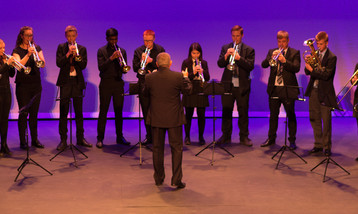 A row of brass players performing on a stage.