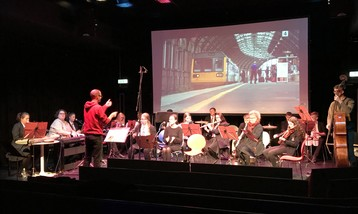 A group of musicians performing in front of a screen showing a film.
