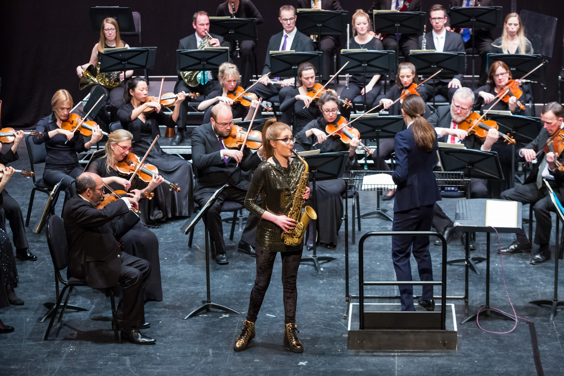 A saxophonist performing with an orchestra.