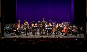 An orchestra on stage made up of participants and professional musicians, with a saxophone soloist at the front.