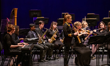 A solo saxophone player in front of an orchestra of students and professional players