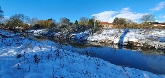 A photograph of a river, with snow covered banks and patches of shadow and sunlight