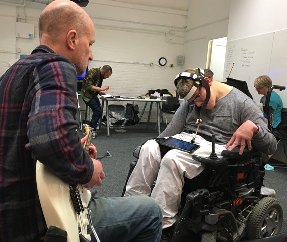A man playing a guitar with a man in a wheelchair using a pointer device attached to a headset.