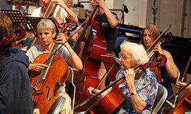 An older woman playing cello in an orchestra,