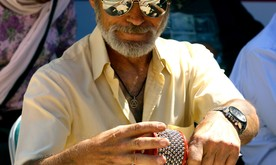 An older man in a hat and sunglasses playing a percussion instrument.