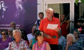 An older man stands in front of some musicians and sings from a sheet of paper.
