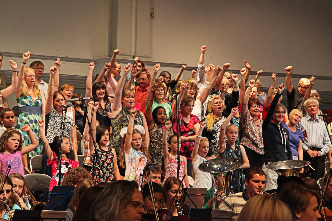 Singers in a choir with their right arms raised.