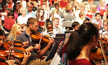 Musicians of a wide range of ages rehearsing in an orchestra.