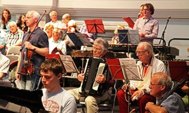 Mid shot of an orchestra with focus on an accordion player