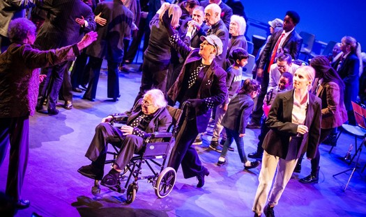 A group of performers on stage including an older woman in a wheelchair in the front.