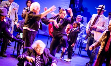 A group of performers on stage dancing with an older woman in a wheelchair in front.
