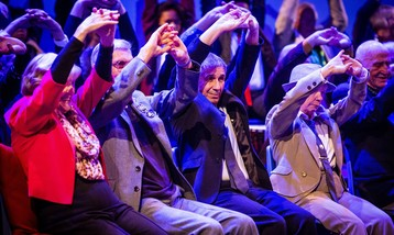 A group of older people stretching their arms above their heads.