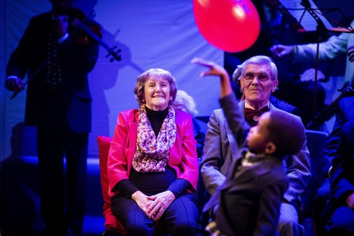 An older man and woman seated watching a young boy playing with a red balloon.