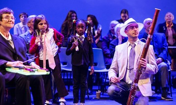 Two young girls playing hand bells on stage, a man in a suit playing bassoon and other performers around playing percussion instruments.