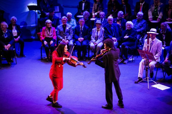 A young woman and young man playing violins on stage facing each other, seated rows of performers behind.