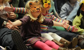 Two young girls with animals masks sat on the floor gesturing with their arms open.