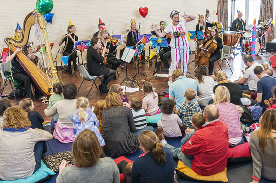An audience of young children and adults watching a presenter and orchestra.