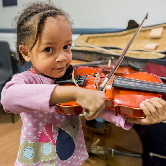 A young girl playing a violin