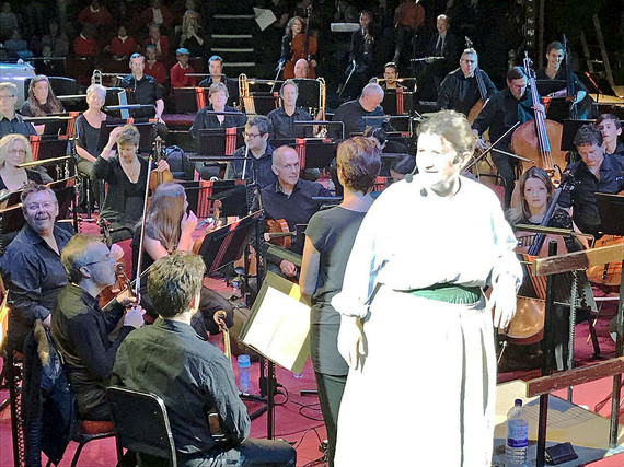 A woman in costume and a headset microphone in front of a large orchestra
