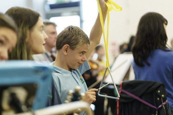 A boy playing a triangle, held on a yellow ribbon above his head.